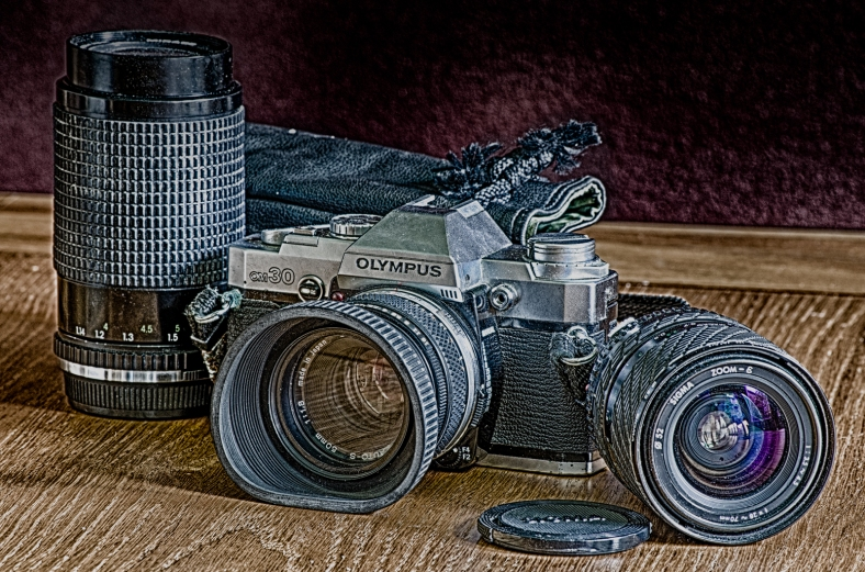 HDR image of an old Olympus OM30 camera and lenses.