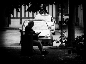 A man sat in the shade, reading a book.