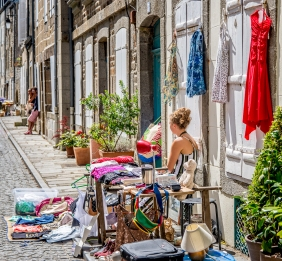 Waiting: a young woman waiting to sell her goods at a street stall in France.